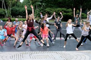 A picture of our Artistic Director Laura NIghtingale jumping with arms stretched above the head. She is wearing black leggings a burgundy top with a red jumper tied around her waist. She is leading a session of to a group of young people who are following her lead.