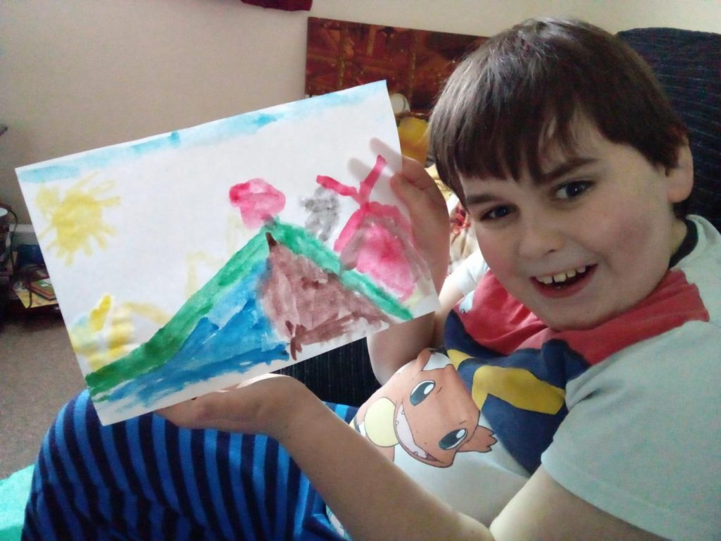 A picture of a young person who attends our sessions holding a painting he created. He is smiling and wearing a white t-shirt and blue and black striped trousers.