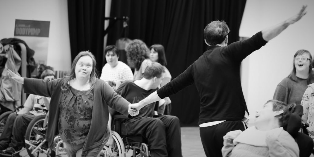 Description: A black and white photo of people in a dance session, in the centre there are two people holding hands dancing. In the background there are several people partaking in the class having a good time.