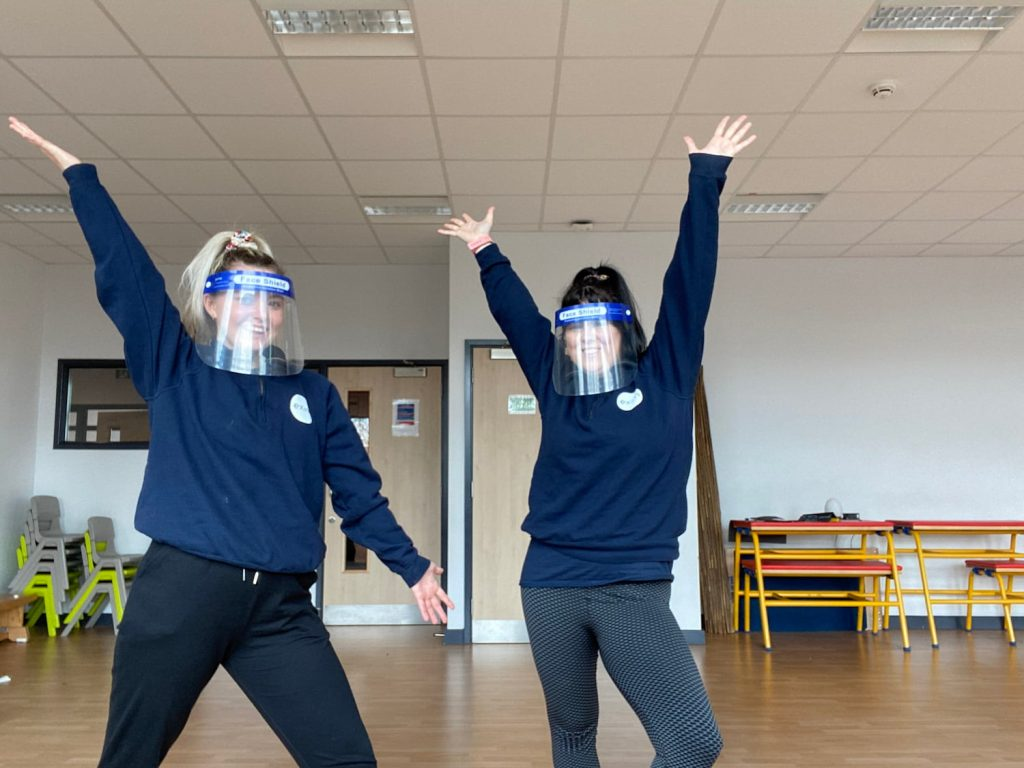 Hayley and Chloe in a school ready to teach, they are both wearing navy Exim jumper's & black trousers.
