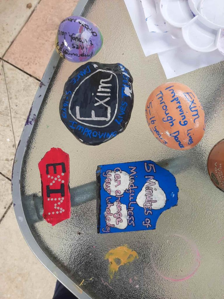 A picture of 5 stones which are all painted colourfully with different quotes on each one.